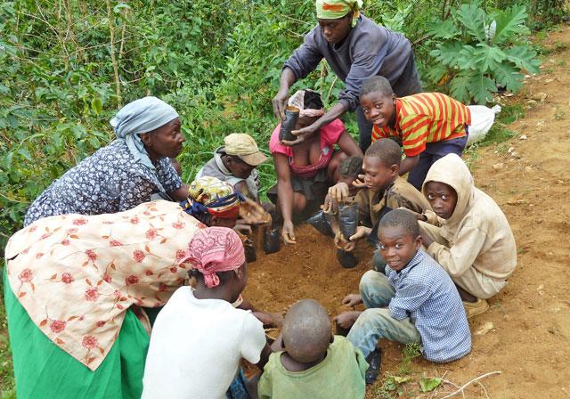 Foto: Frauen und Kinder füllen die vorgemischte Erde in Pflanztütchen