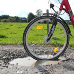Foto: Fahrrad fährt in Schlagloch