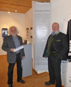 Der Vorsitzende des Auerbergmuseums Helmut Gehlert (rechts) und der Autor Hans Schütz, dazwischen das Textbanner mit der »Ballade von der Vertreibung der Römer vom Auerberg« Foto: Heinz Engl
